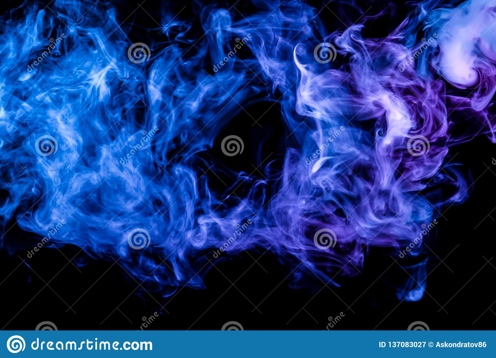 Clubs of colored smoke of blue and pink color on a black isolated background in the form of clouds from the vape