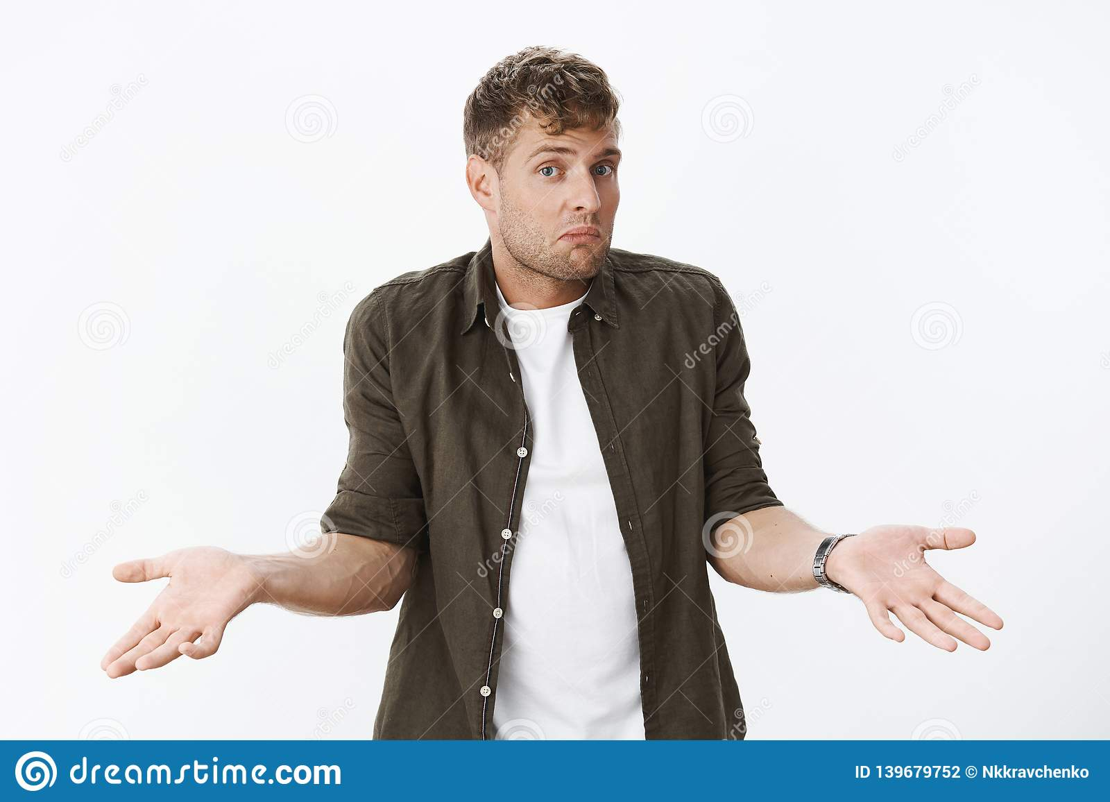 Clueless guy shrugging shoulders as being unaware. Portrait of confused cute blond man holding hands sideways dazed