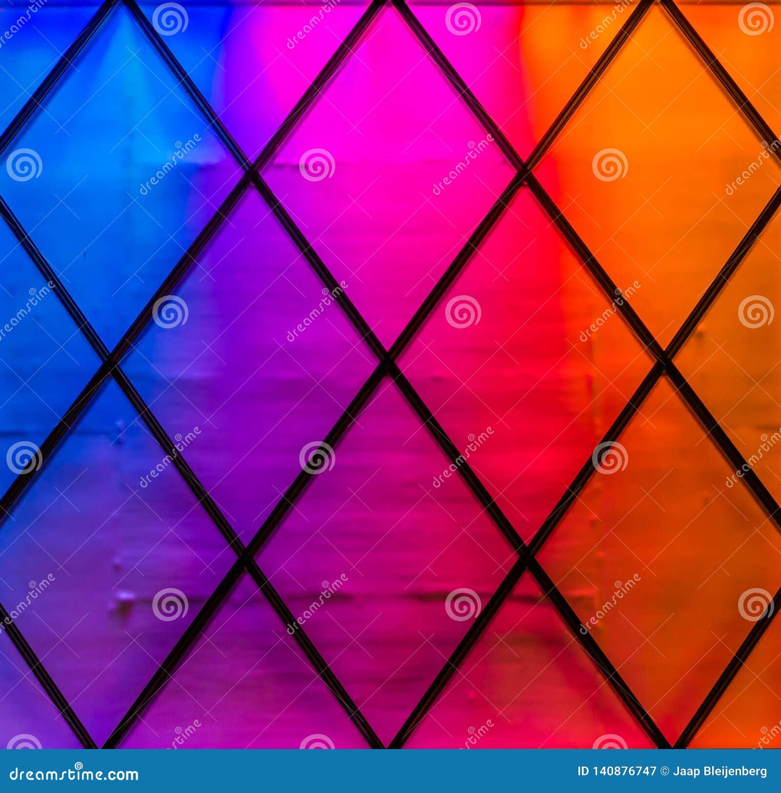 Современные и красочные света в цветах голубых, пурпурных, пинке, красном и оранжевом Ромбовидный узор, предпосылка неонового све