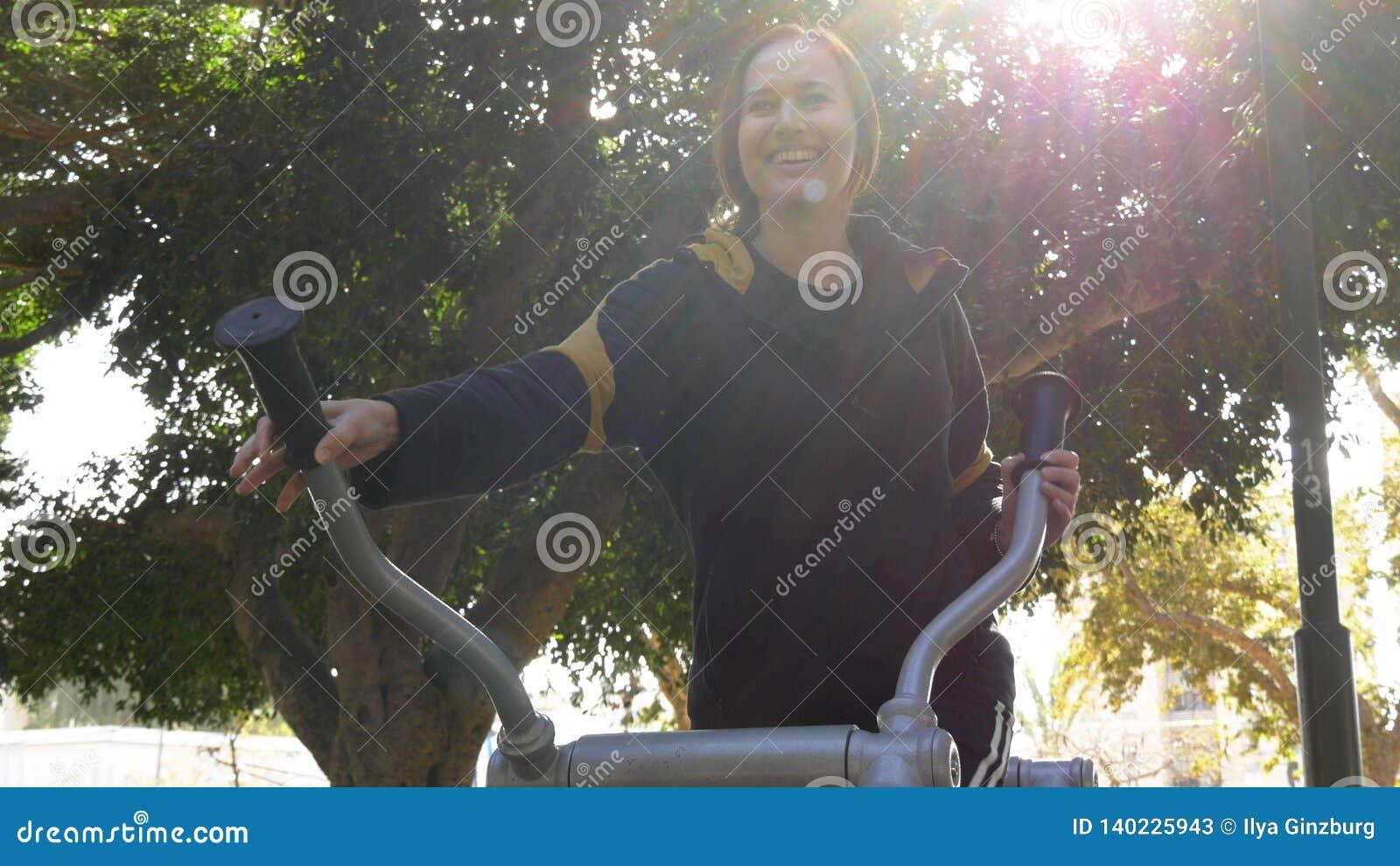 Солнечная усмехаясь женщина, который побежали на приборе для тренировки