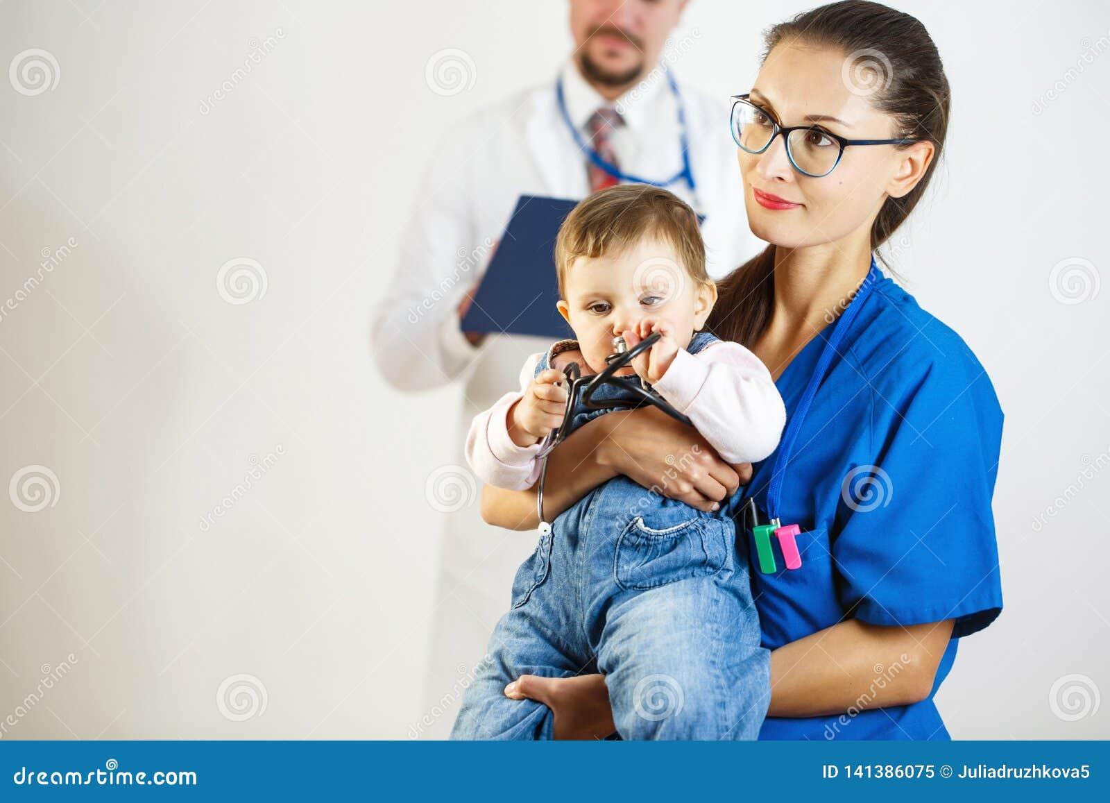Сонные детские игры со стетоскопом на руках медсестры, на заднем плане доктор Белая предпосылка