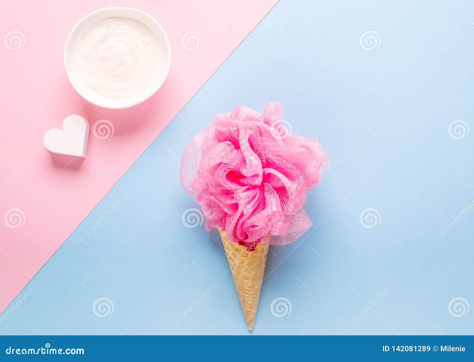 Состав конуса мороженого с розовым пучком мочала на светлом - голубая предпосылка