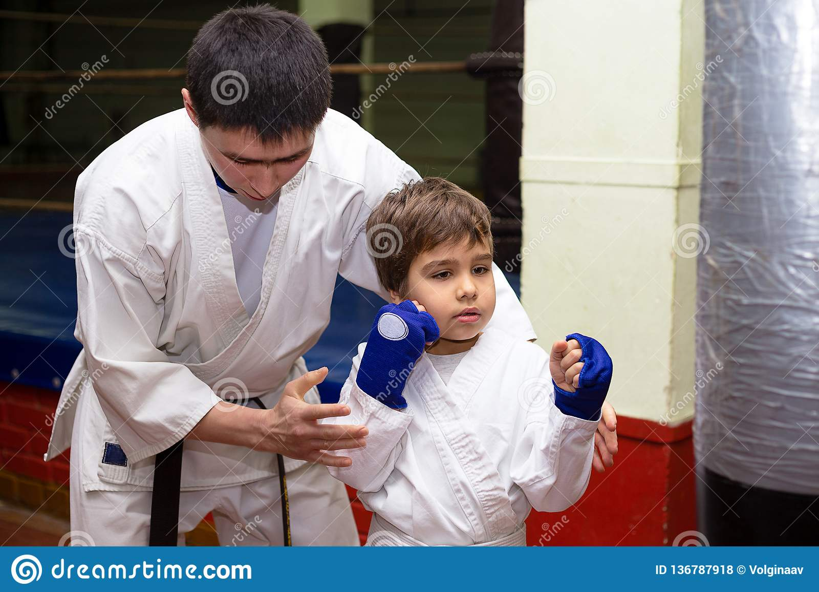 Coach is training young teenagers in karate class