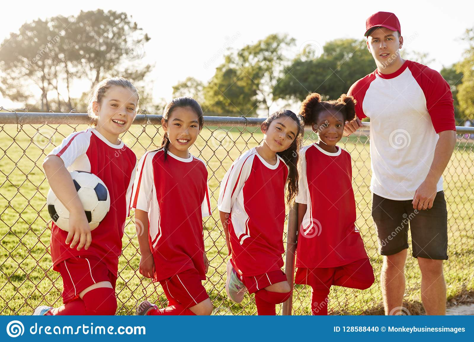 Coach and young girls in a football team looking to camera