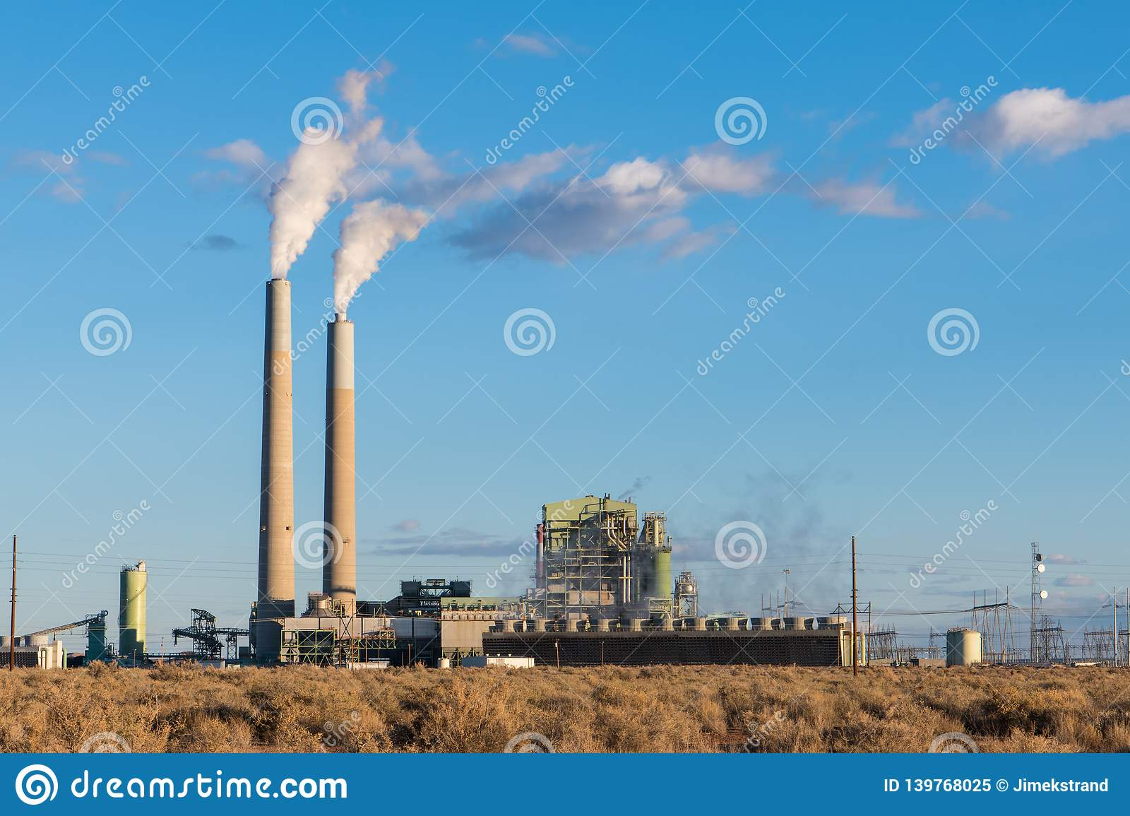 A coal-fired electrical power plant with smokestacks emitting plumes of smoke in the southwestern United States