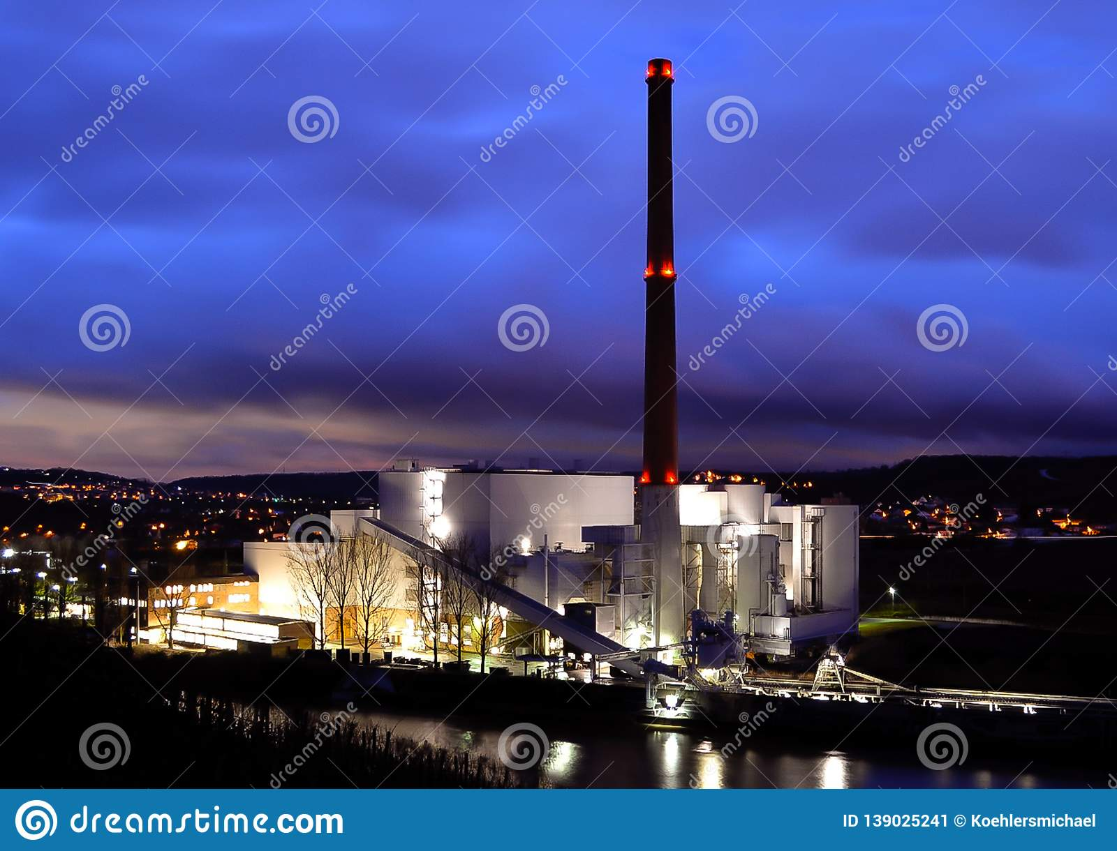 Coal-fired power plant at night with cloudy sky
