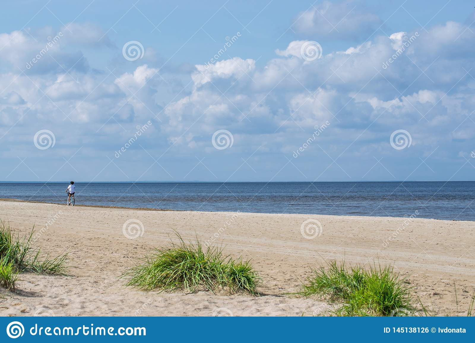 Coast of beach with lonely cyclist in the bright sunny day. Sunny bright day with white clouds.