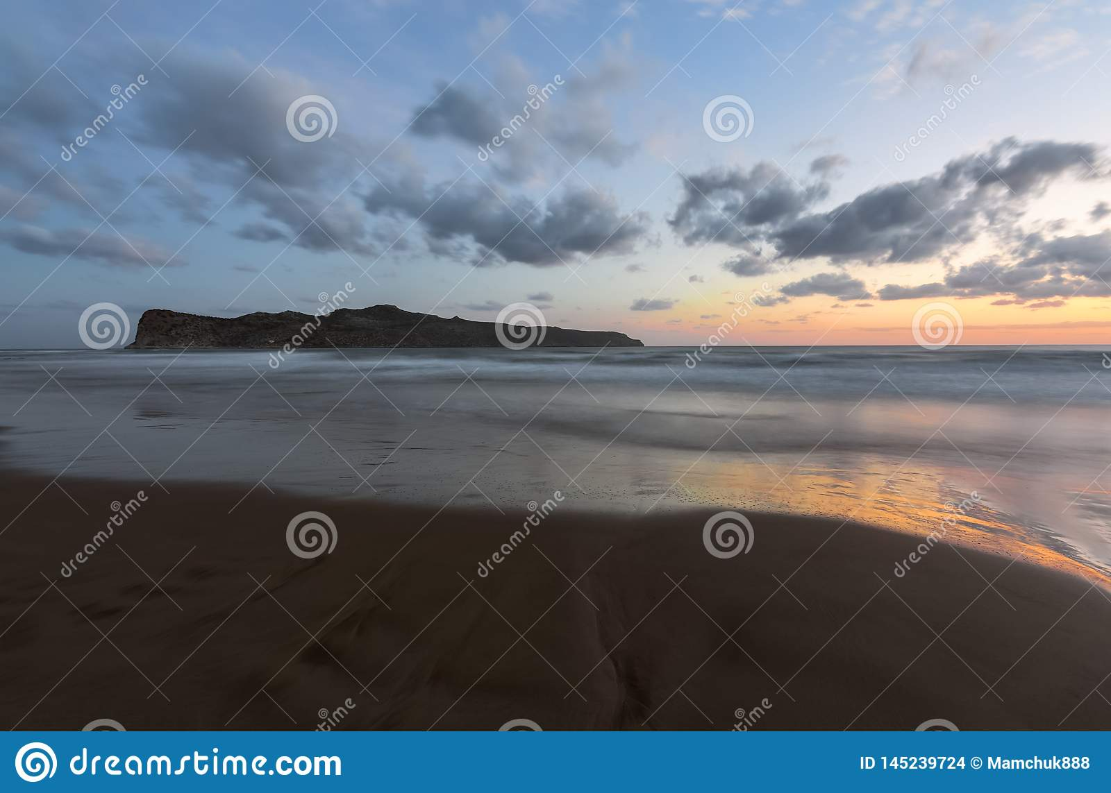 From the coast with wet sand, sea with waves, mountains there is a fantastic view of sunset sky that lights up with unbelievable.