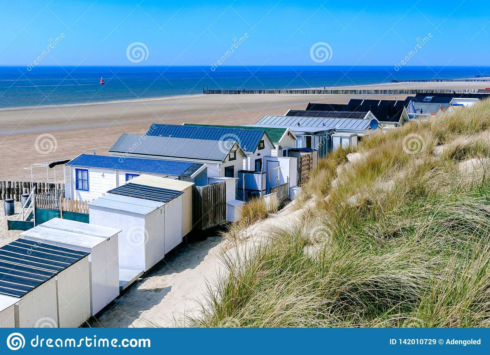 Coastal view with vacation homes, dunes, empty beach, blue sea and clear sky.