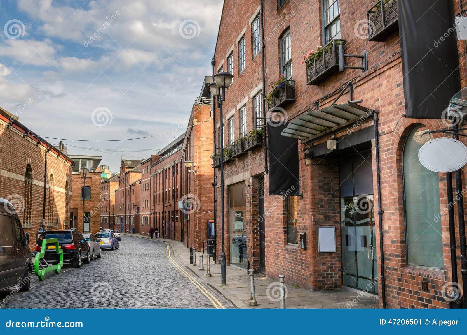 Cobbledstraat met Baksteengebouwen dat wordt gevoerd