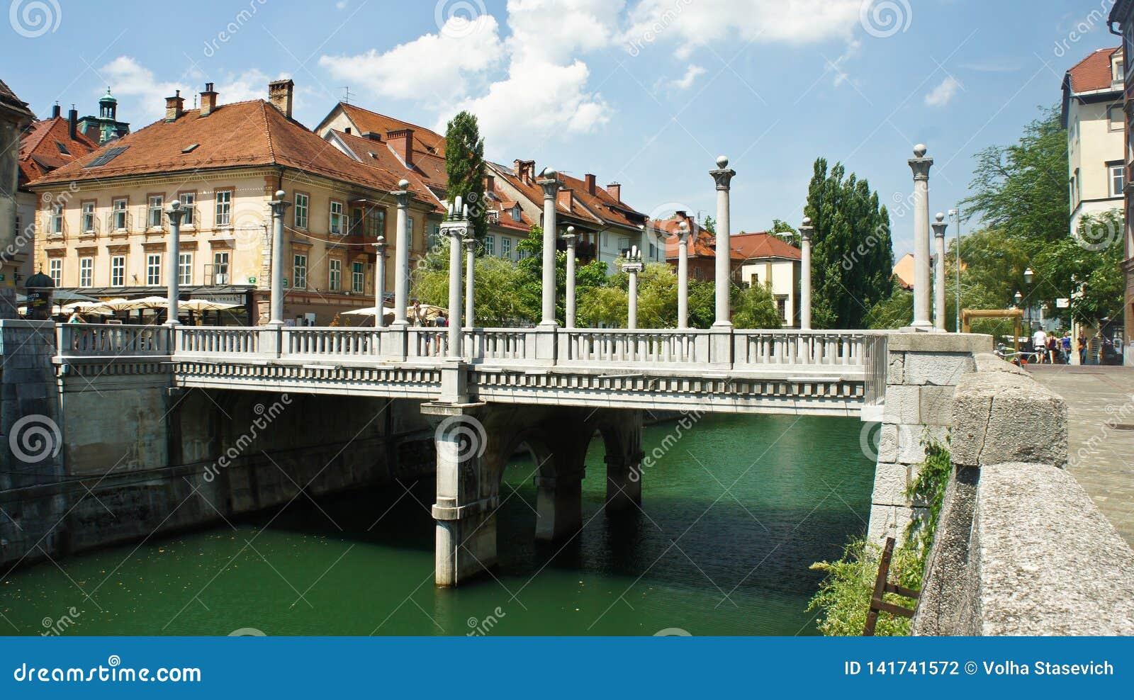 Ljubljana, Slovenia - 07/19/2015 - The Cobbler`s Bridge with Corinthian and Ionic pillars as lamp-bearers, sunny day