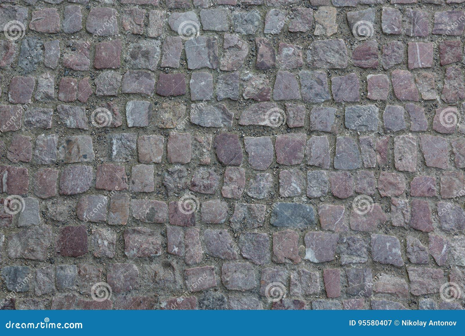Cobblestoned granittrottoar för bakgrund Stentrottoartextur Abstrakt bakgrund av den gamla kullerstentrottoarnärbilden i Prag