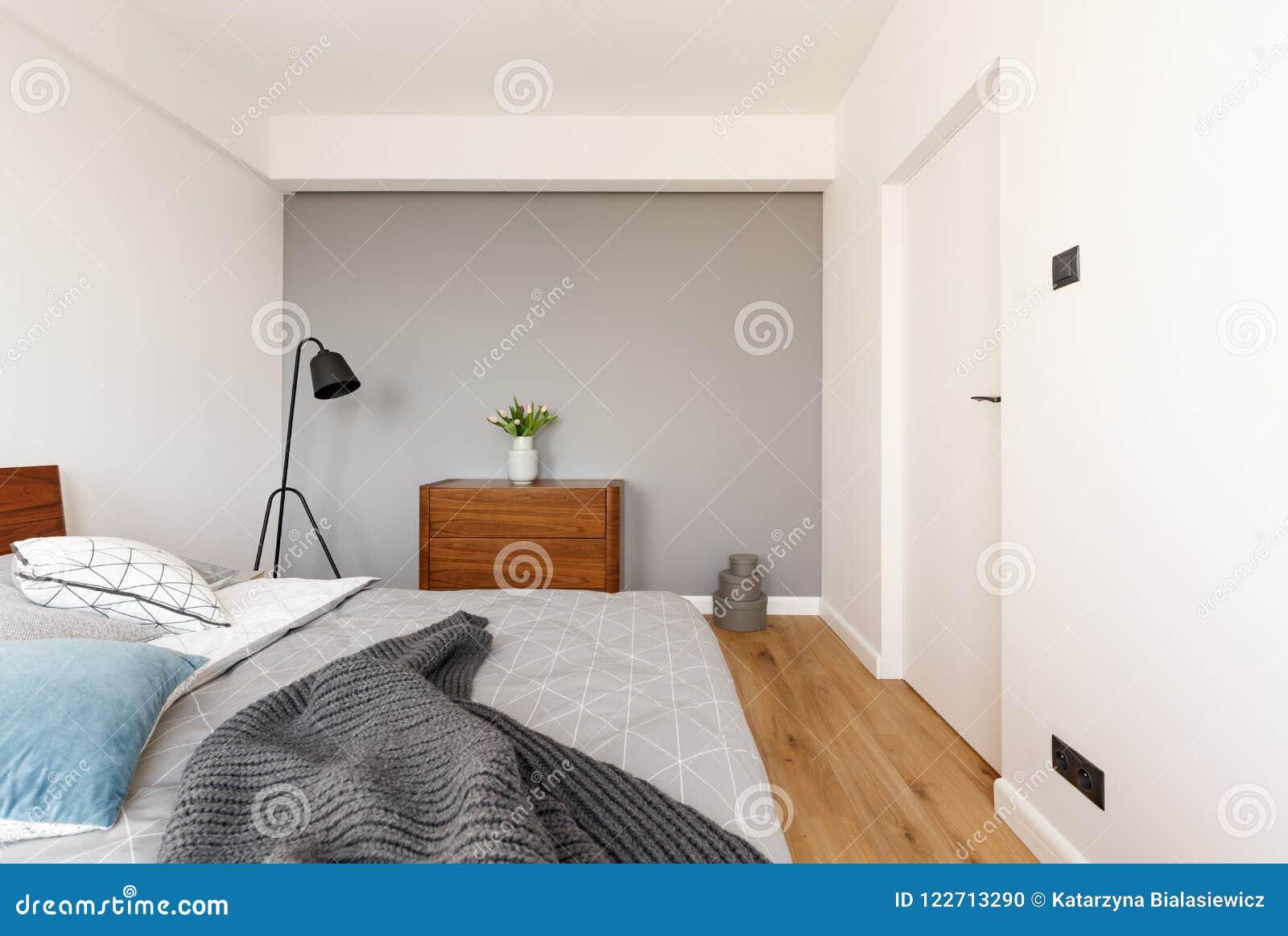 Cobertura cinzenta na cama no interior mínimo do quarto com a planta no Ca