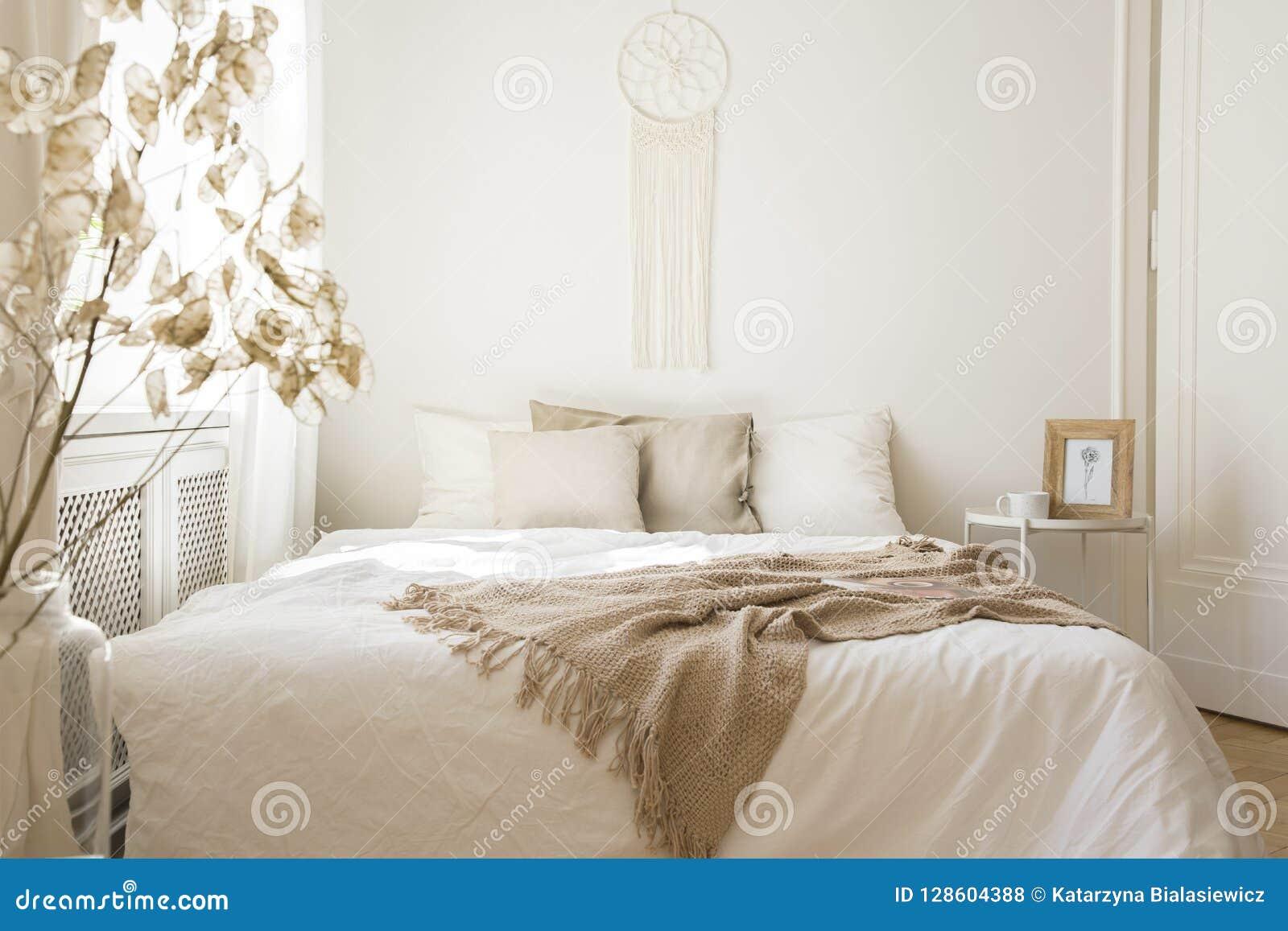 Cobertura na cama branca com os coxins no interior mínimo do quarto com planta e tabela