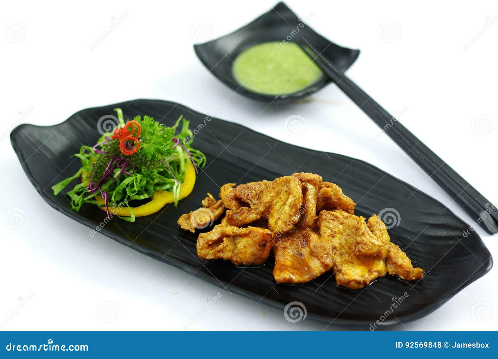 Coccodrillo arrostito con la salsa e l insalata di peperoncino rosso del burro