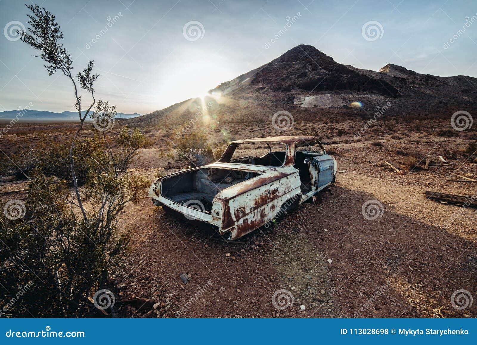 Coche abandonado oxidado viejo en el desierto en el tiempo de la puesta del sol