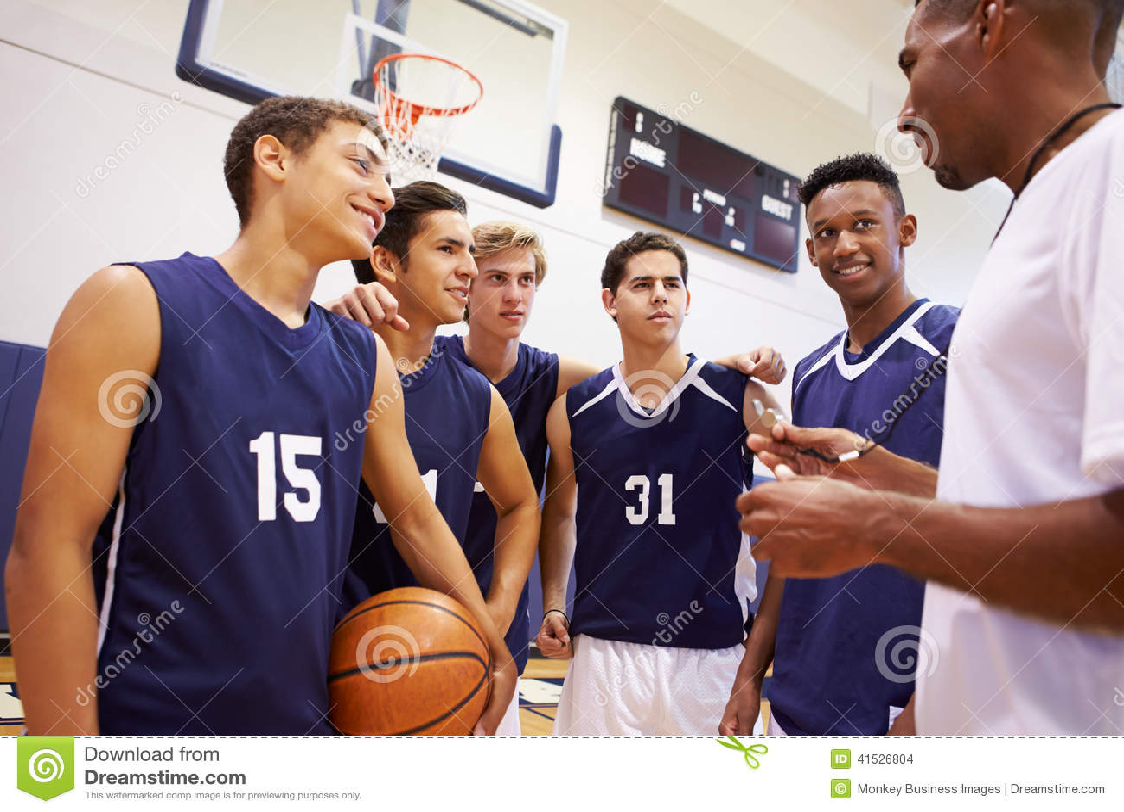 Coche masculino de Team Having Team Talk With del baloncesto de la High School secundaria