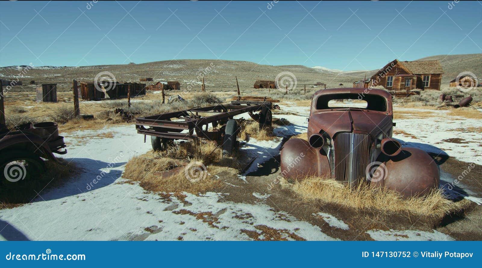 Coche oxidado del vintage en un pueblo abandonado