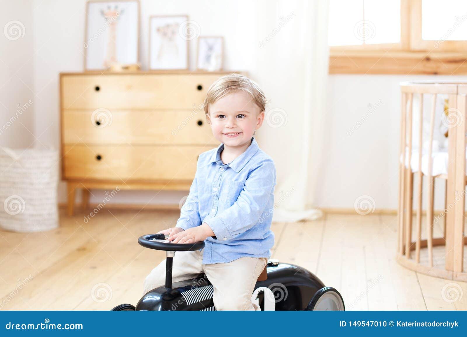 Coche sonriente del vintage del juguete del montar a caballo del niño del retrato Ni?o divertido que juega en casa Vacaciones de