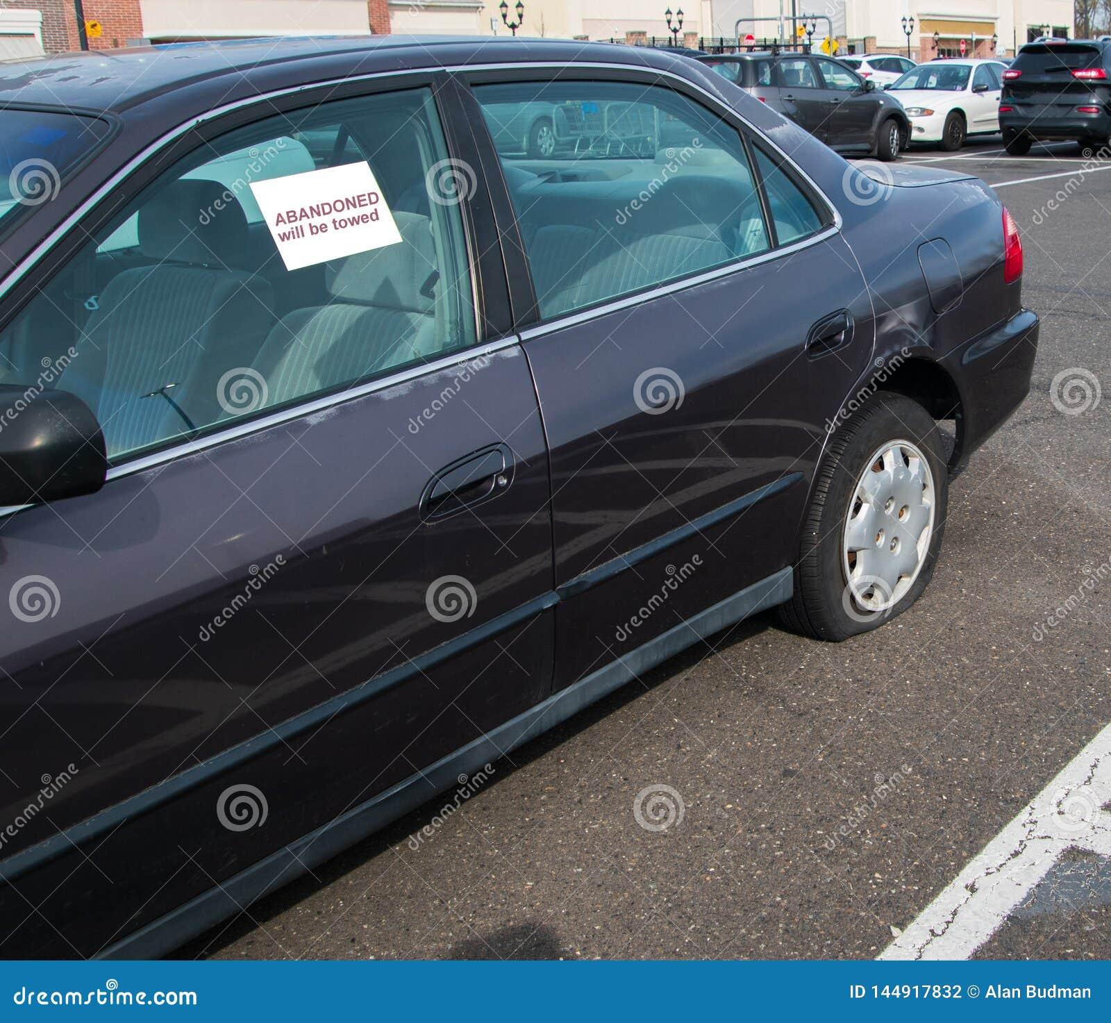 Coche viejo con el neumático desinflado en estacionamiento con la etiqueta engomada en la ventana que dice abandonado
