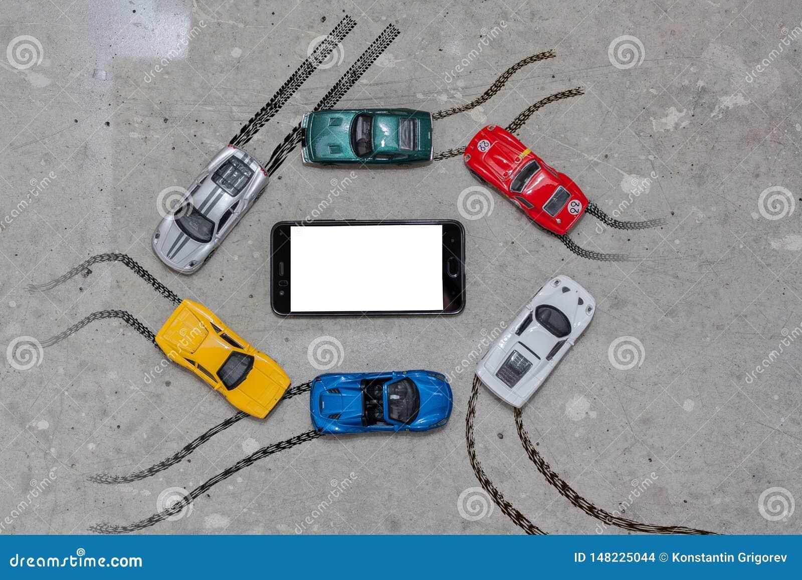 Coches coloreados multi del juguete alrededor de una opinión de top del teléfono móvil