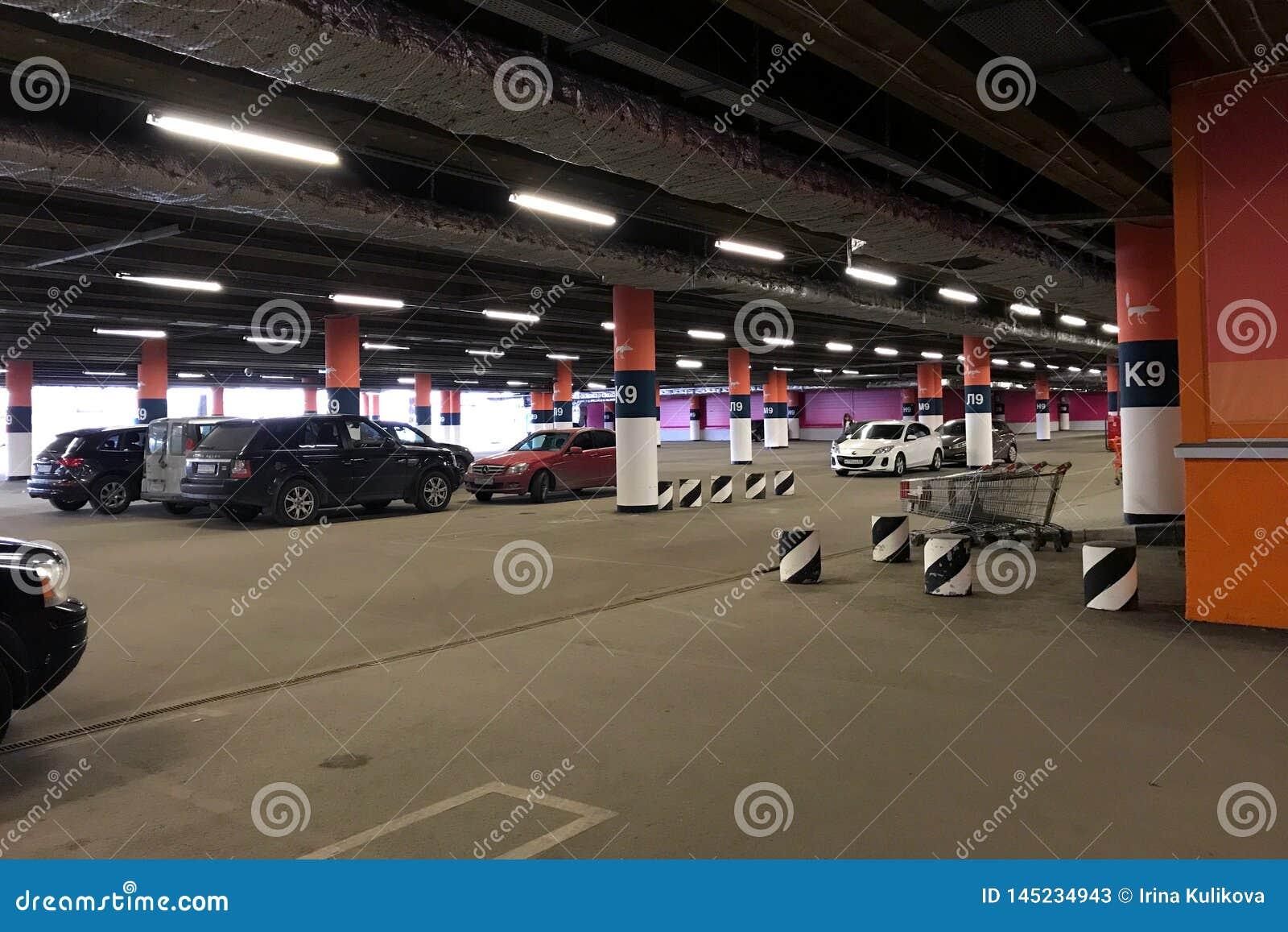 Coches en un aparcamiento subterráneo grande en el centro comercial mega