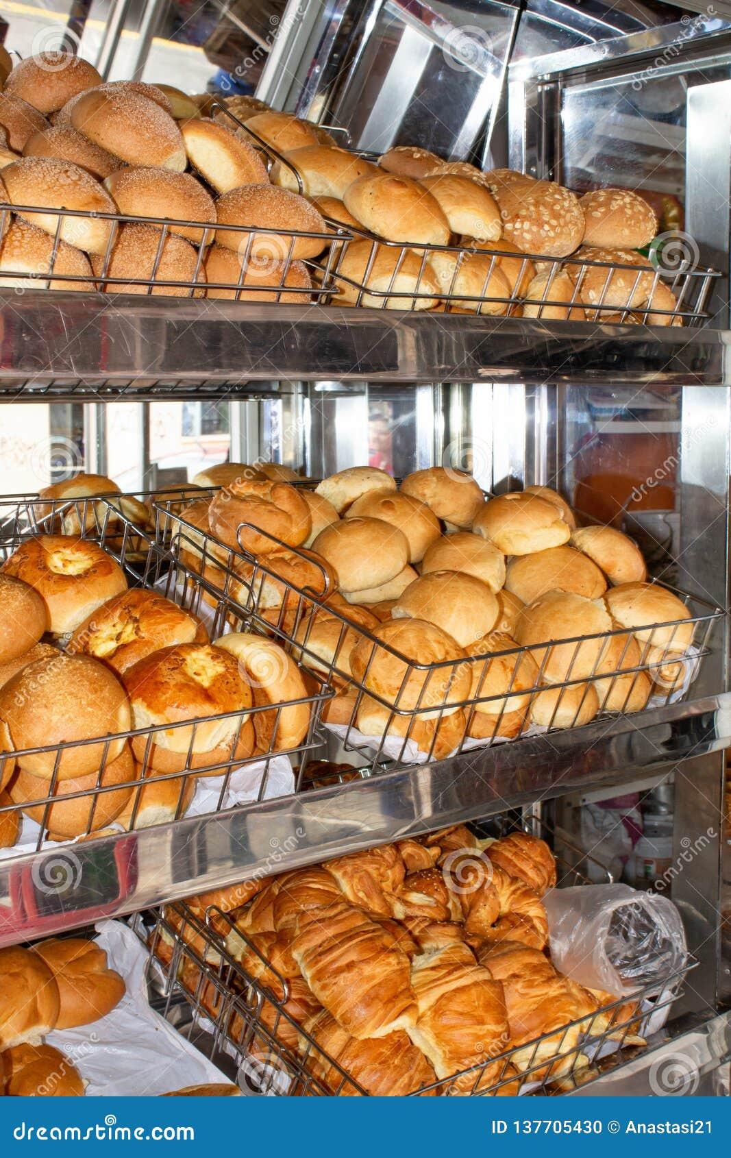 Coció recientemente el pan, estantes con los bollos en la vitrina Quito, Ecuador