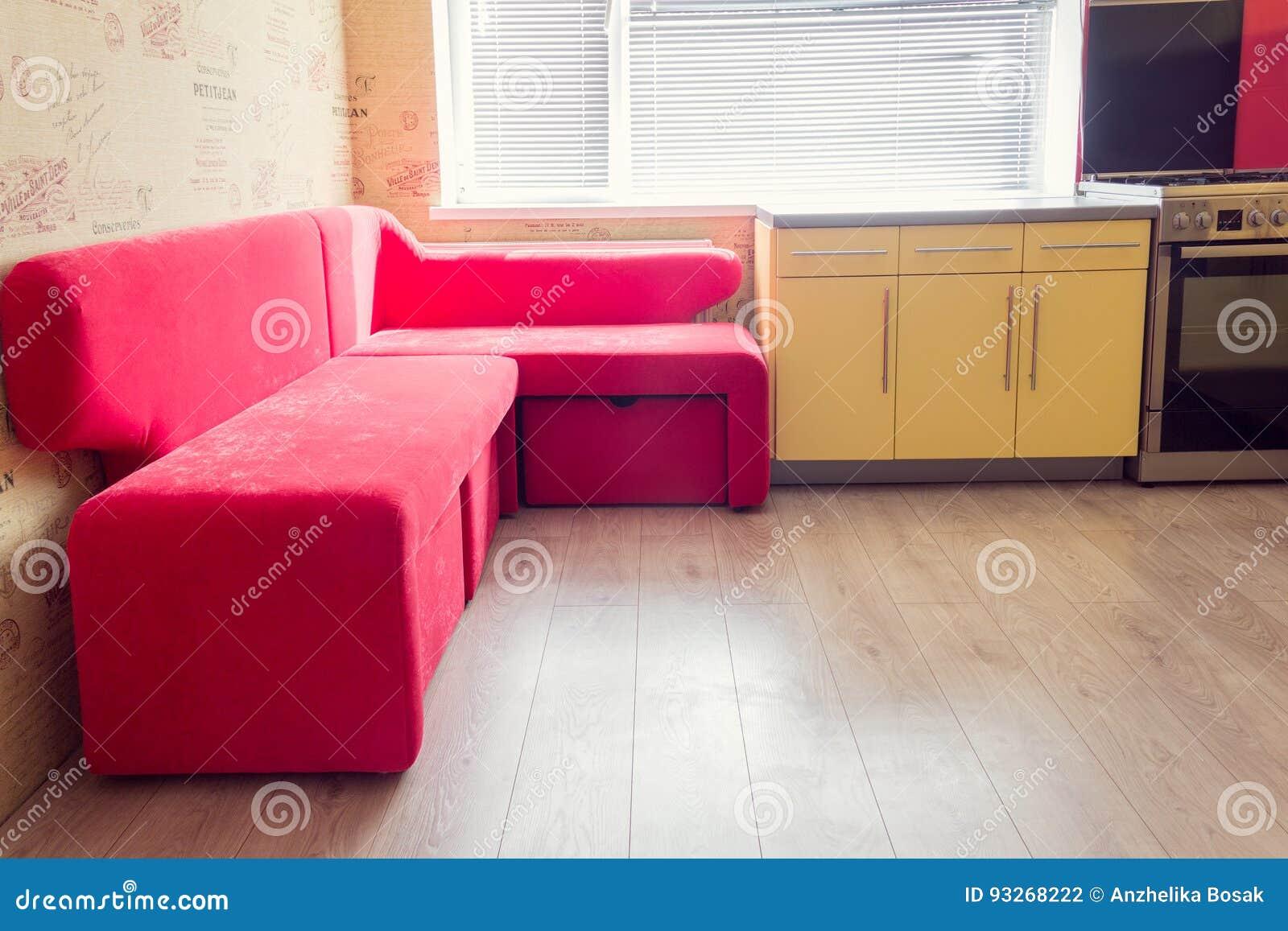 Cocina amarilla con el sofá suave de los armarios, de la ventana, laminado y rojo