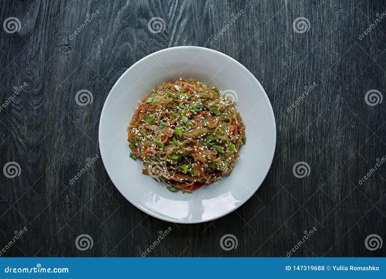 Cocina asi?tica Ensalada de los tallarines del celof?n, frita con las verduras, adornadas con verdes y palillos del cangrejo Func