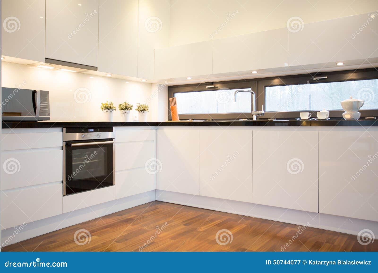 Cocina blanca con el piso de madera imagen de archivo for Cocina blanca y madera moderna