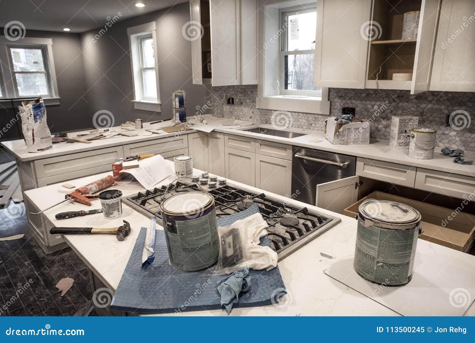 Cocina casera sucia durante el remodelado de la casa que necesita reparaciones con las puertas de armario de cocina