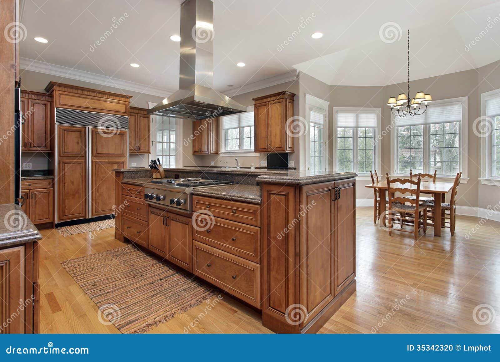 Cocina con la isla de centro de madera y del granito foto for Isla cocina madera
