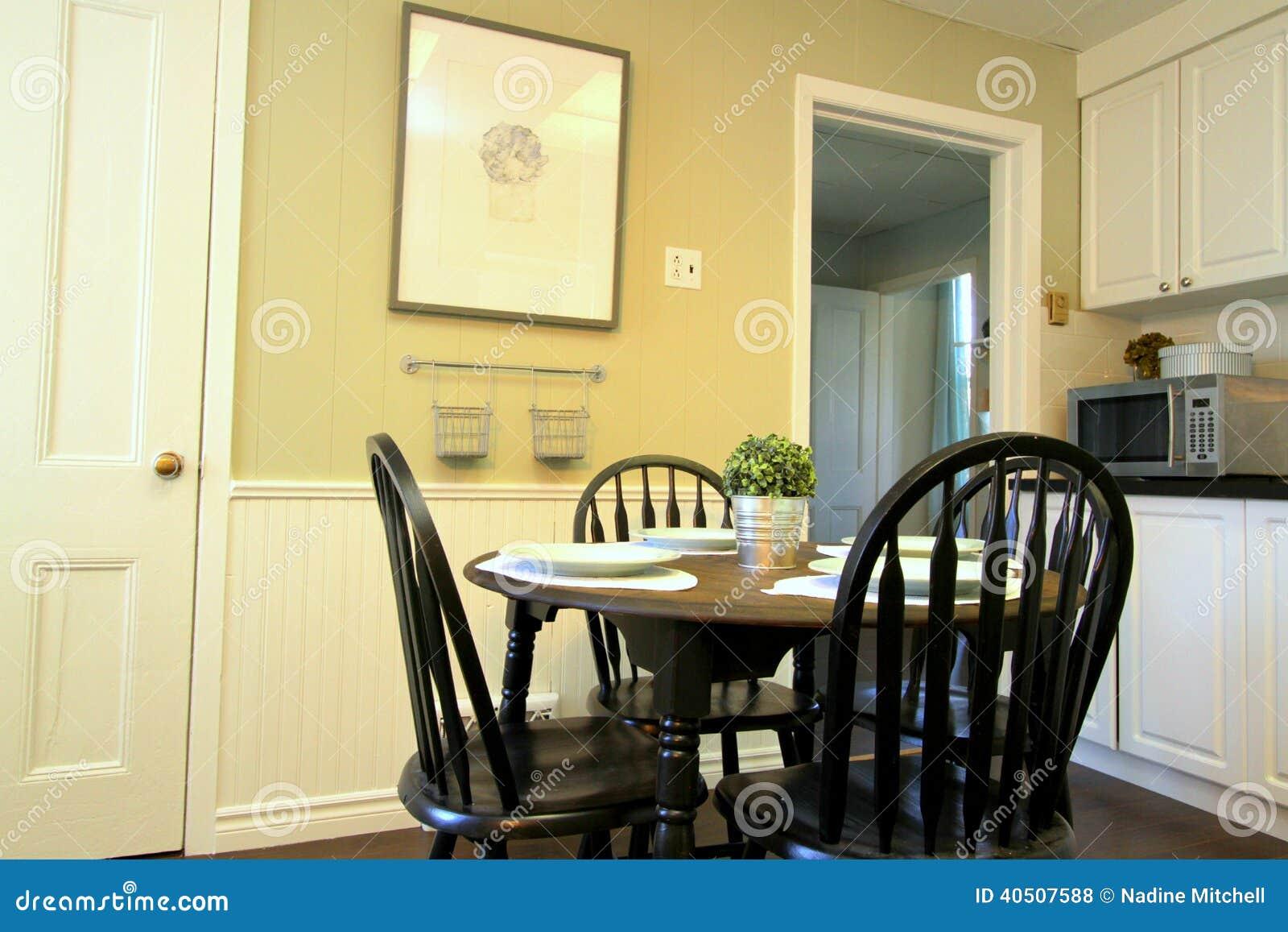 Cocina con los gabinetes blancos y mesa redonda y sillas for Almohadones para sillas windsor