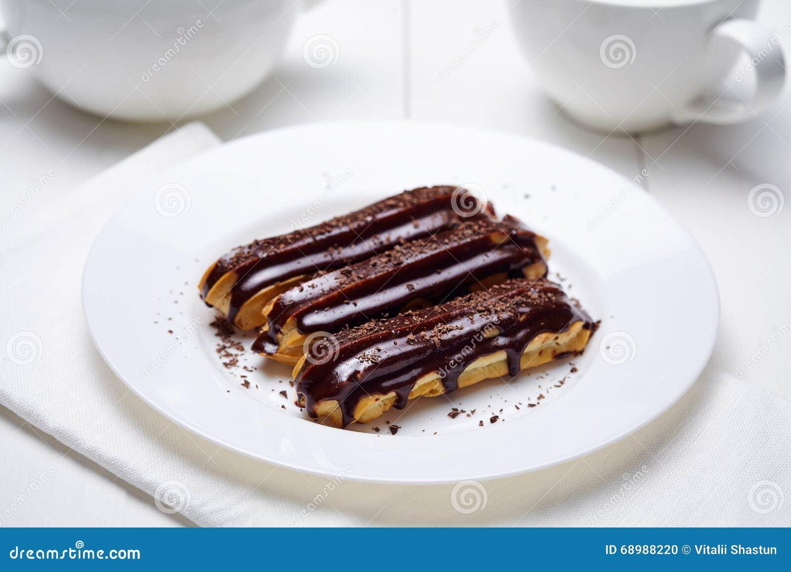 Cocina francesa hecha en casa tradicional de los Eclairs con el chocolate en el plato blanco
