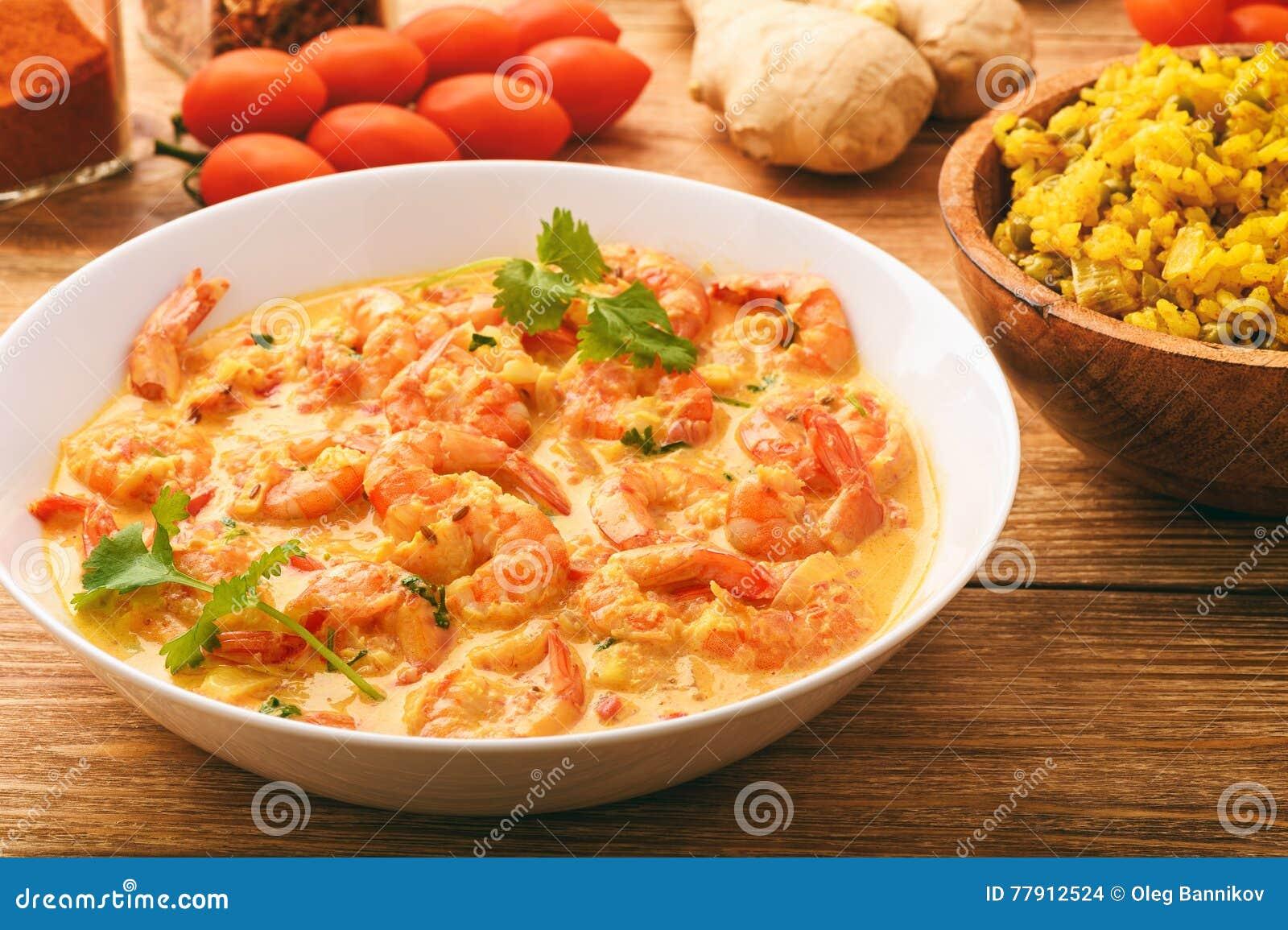 Cocina india - camarones en salsa y arroz del jengibre con curry y el guisante verde