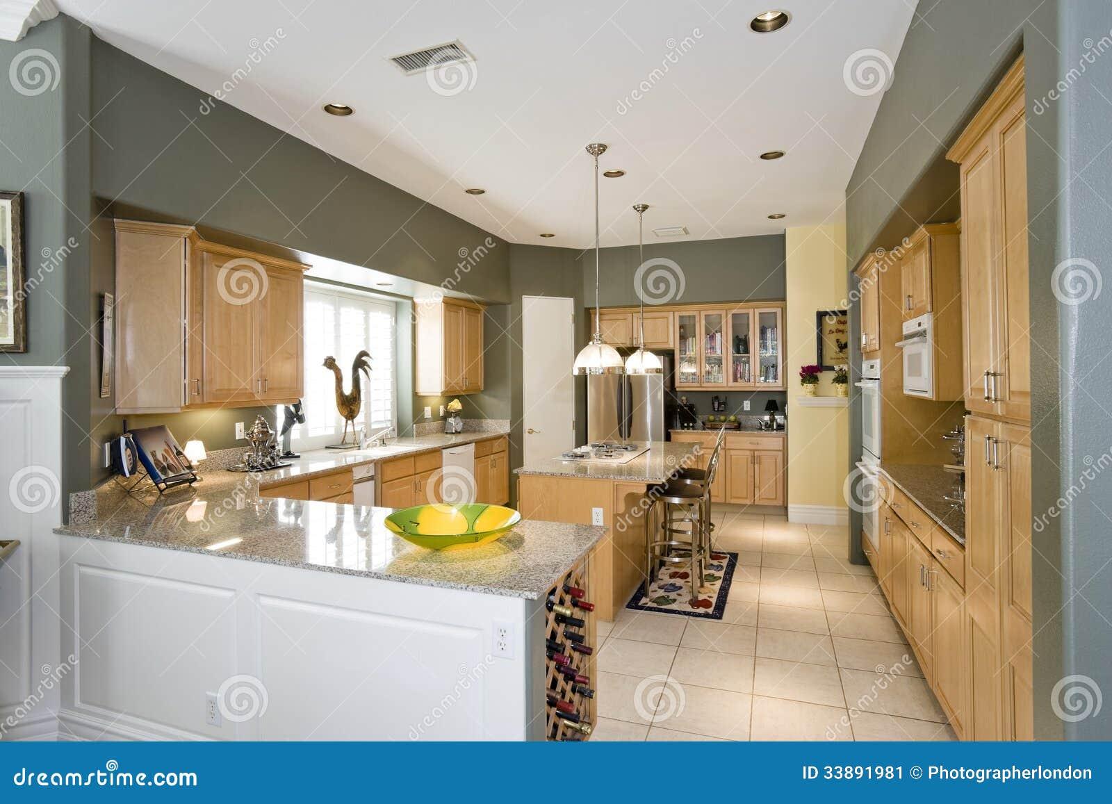 Cocina moderna con los taburetes en la isla en casa imagen for Taburetes isla cocina