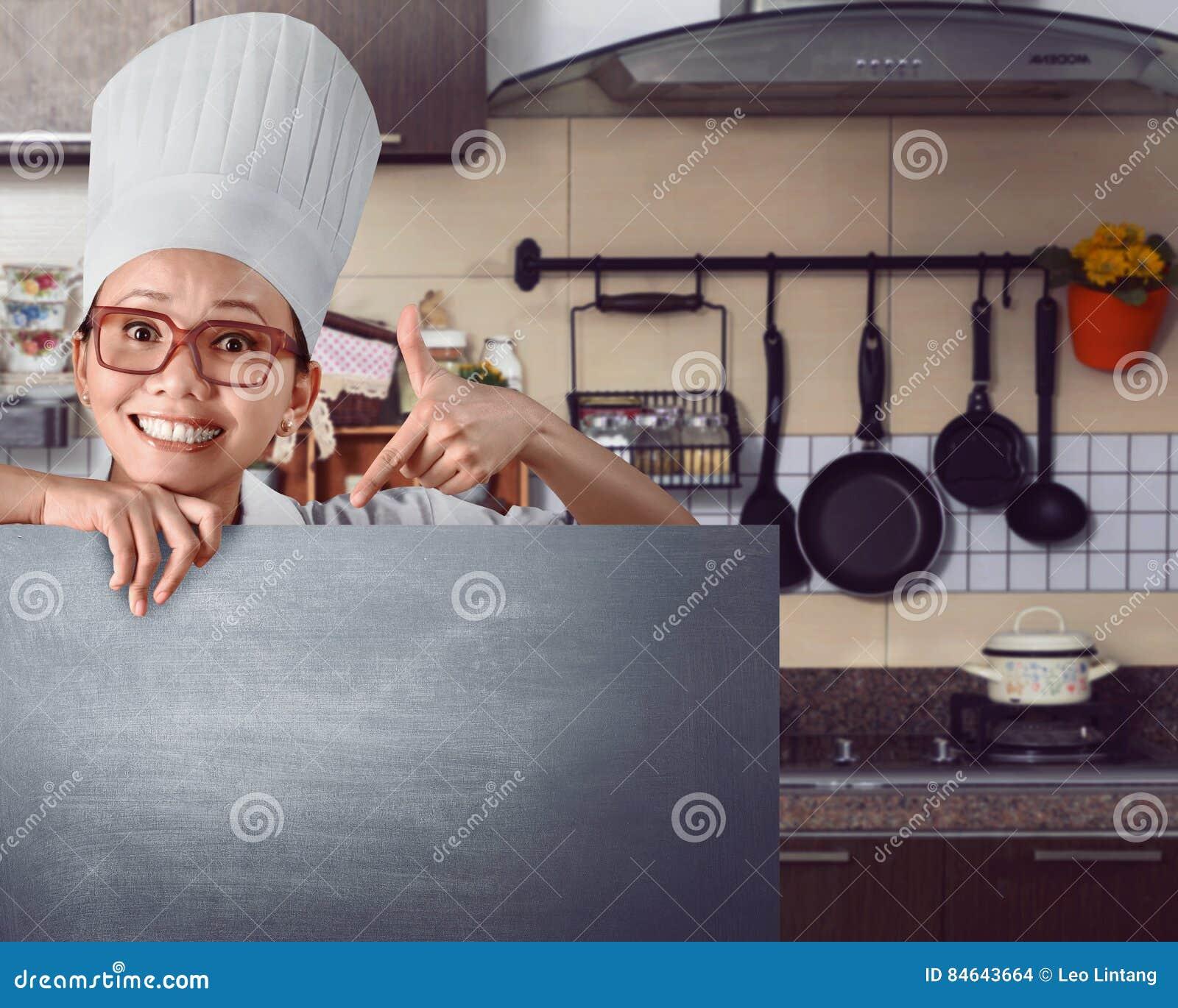 Cocinero asiático feliz que muestra la muestra del menú en la pizarra