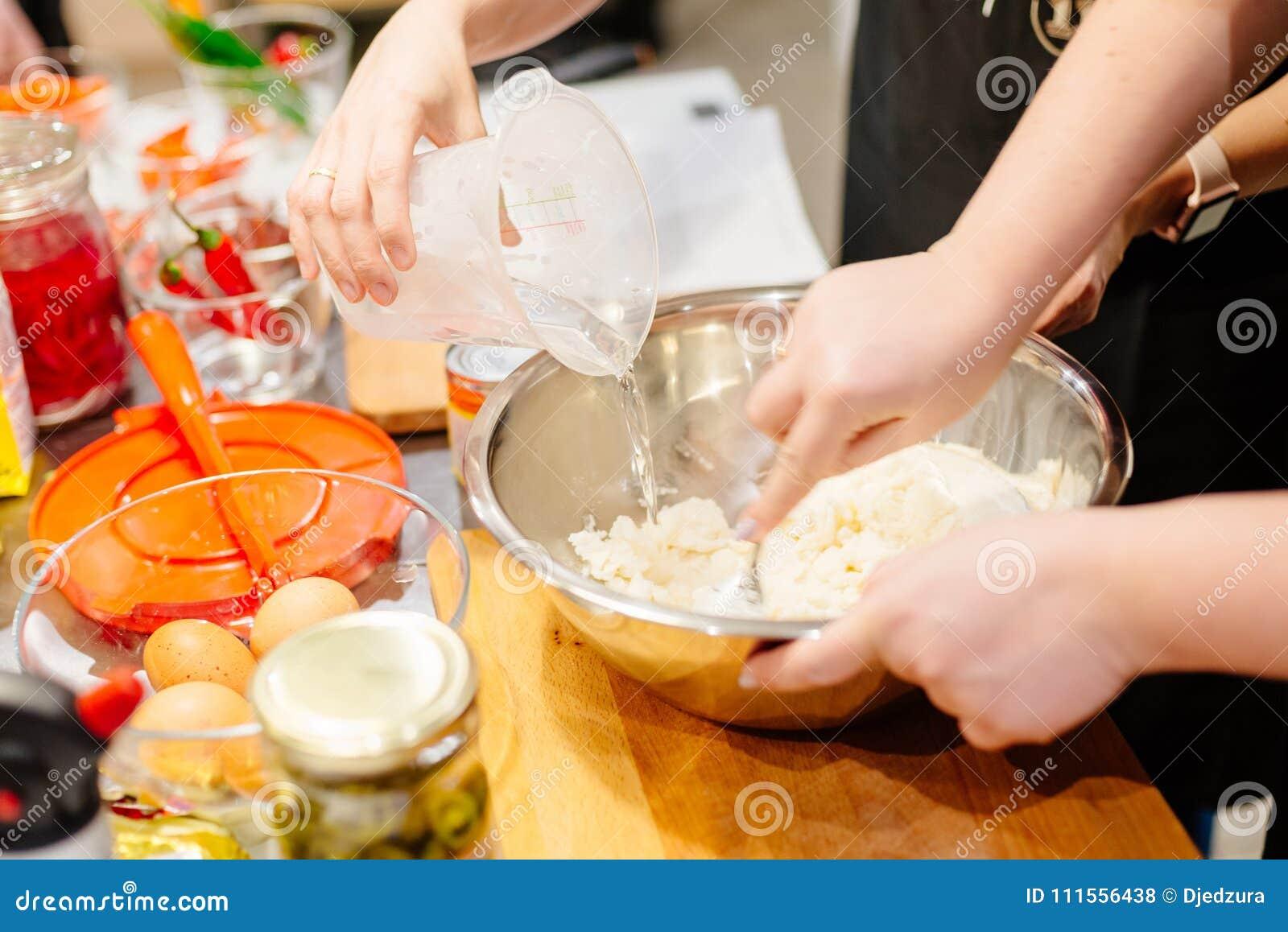 Cocinero de la mujer que prepara la pasta en cuenco