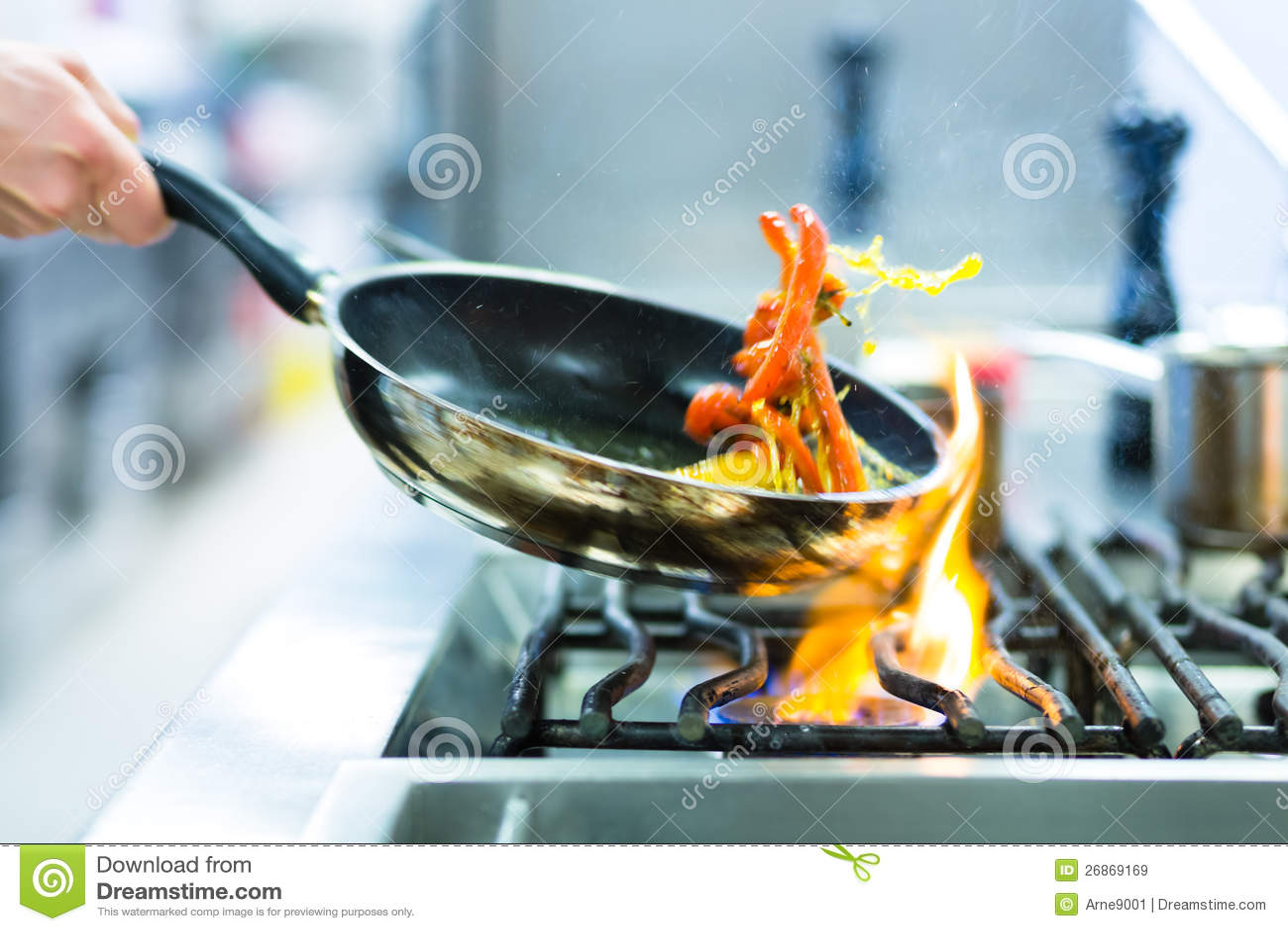 Cocinero en cocina del restaurante en la estufa con la cacerola