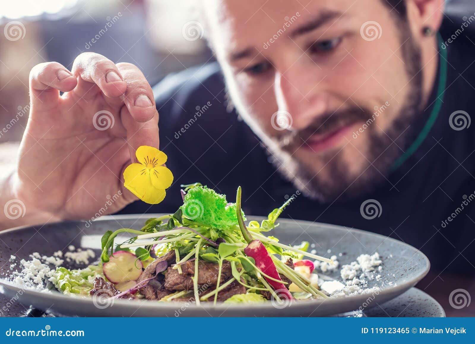Cocinero en el hotel o el restaurante que prepara la ensalada con los pedazos de carne de vaca