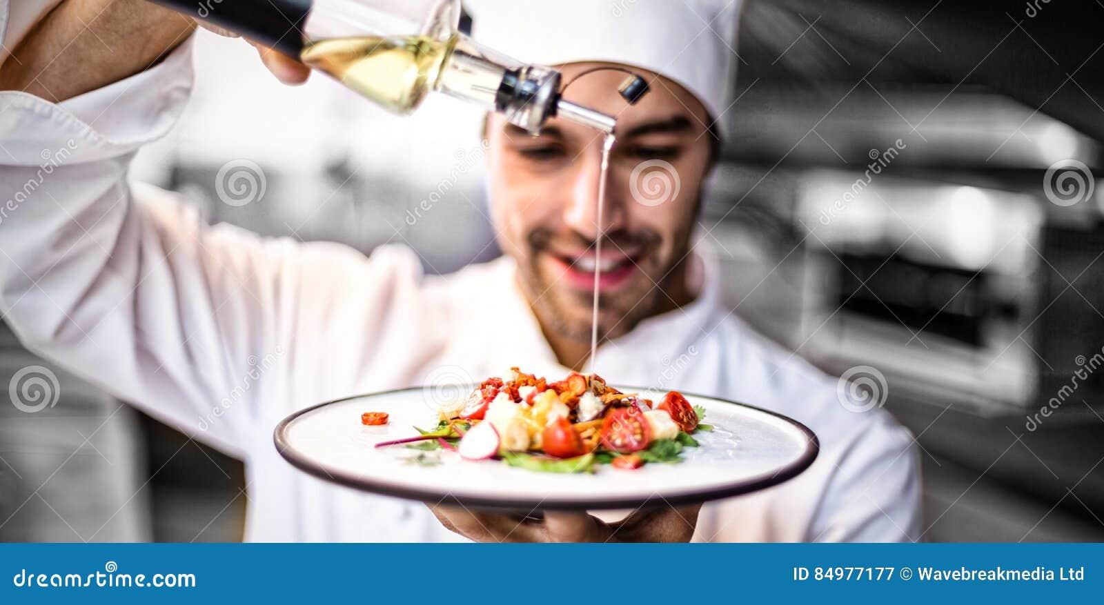 Cocinero hermoso que vierte el aceite de oliva en comida