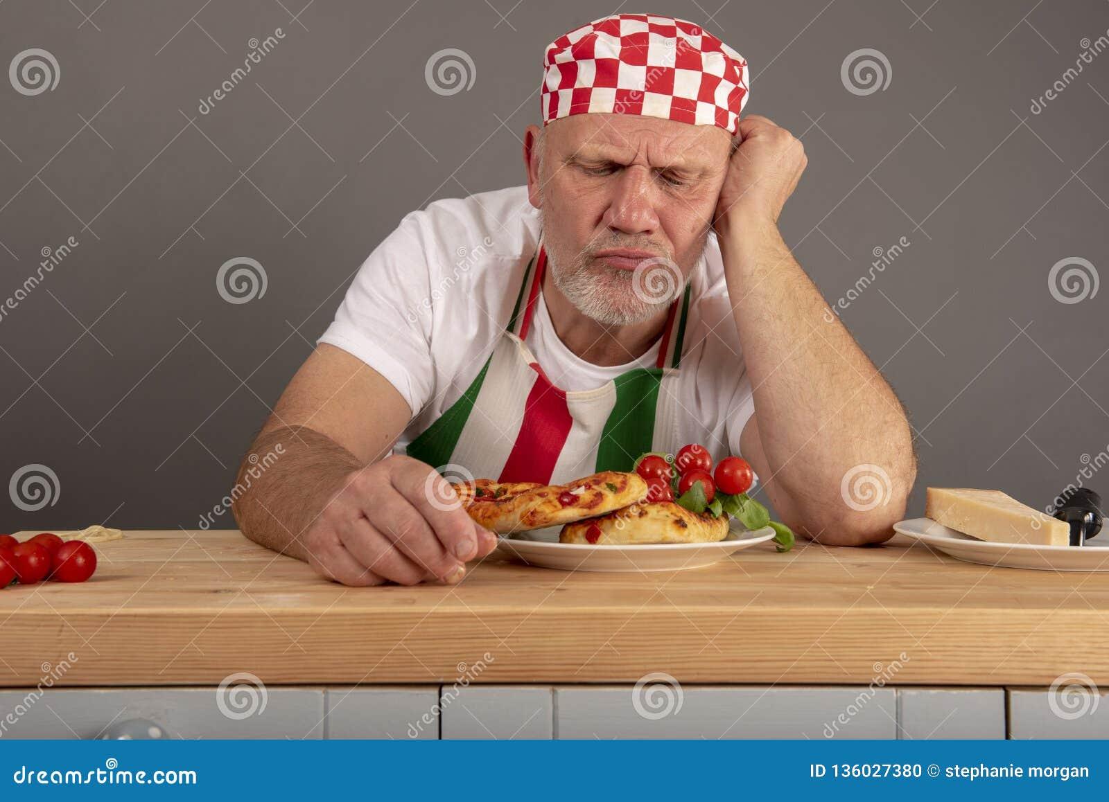 Cocinero italiano maduro que mira una comida que él se ha preparado