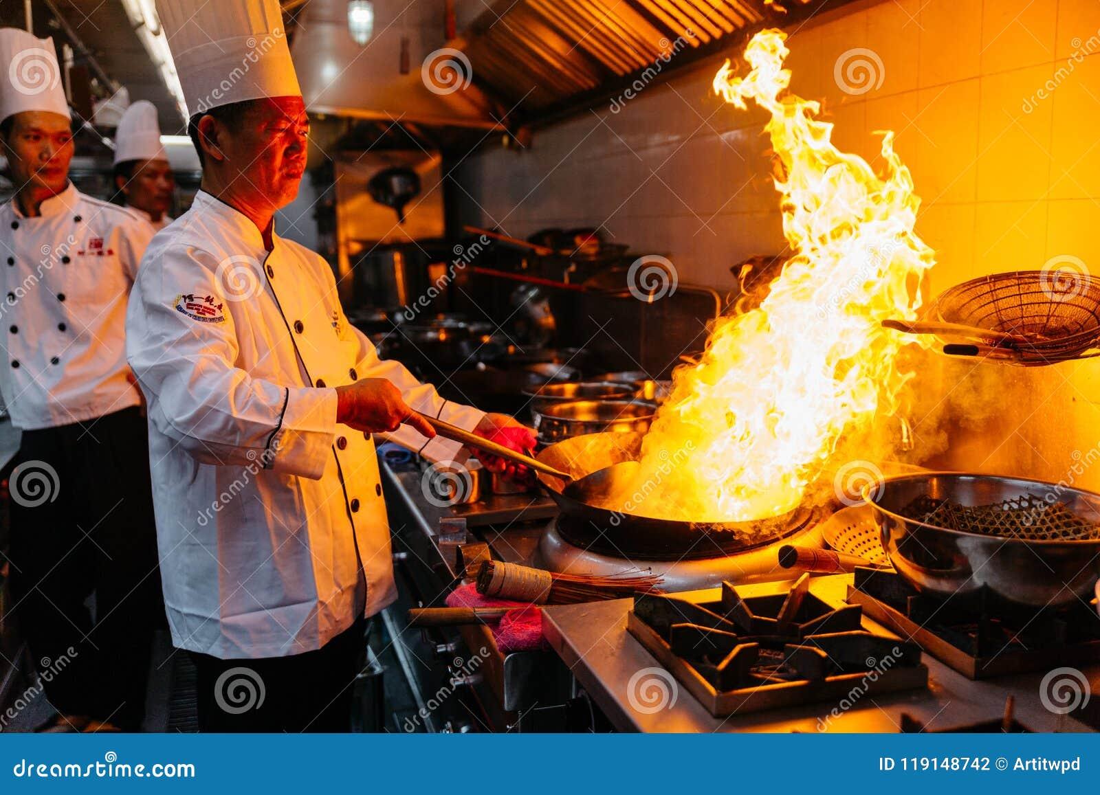 Cocinero que cocina la comida china con el fuego ardiente en la cacerola de acero fotograf a - Cocina de fuego ...