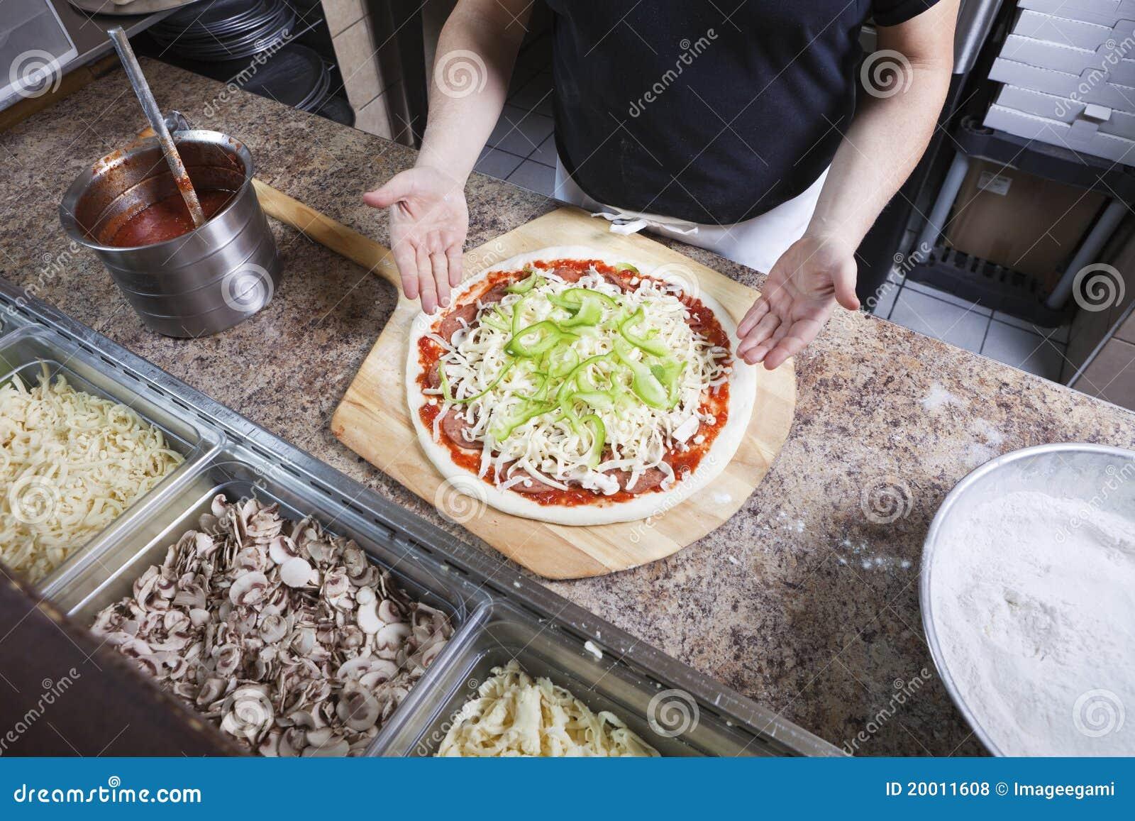 Cocinero que hace una pizza