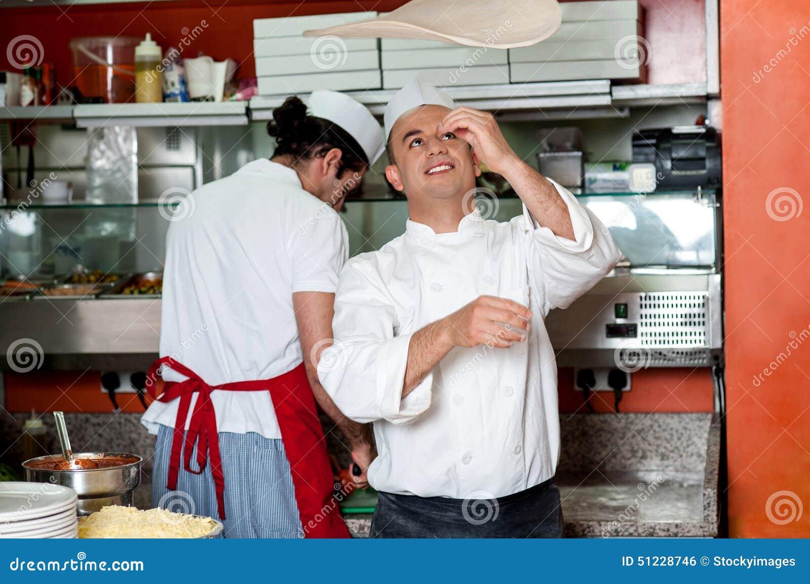 Cocinero que lanza la pasta de la base de la pizza