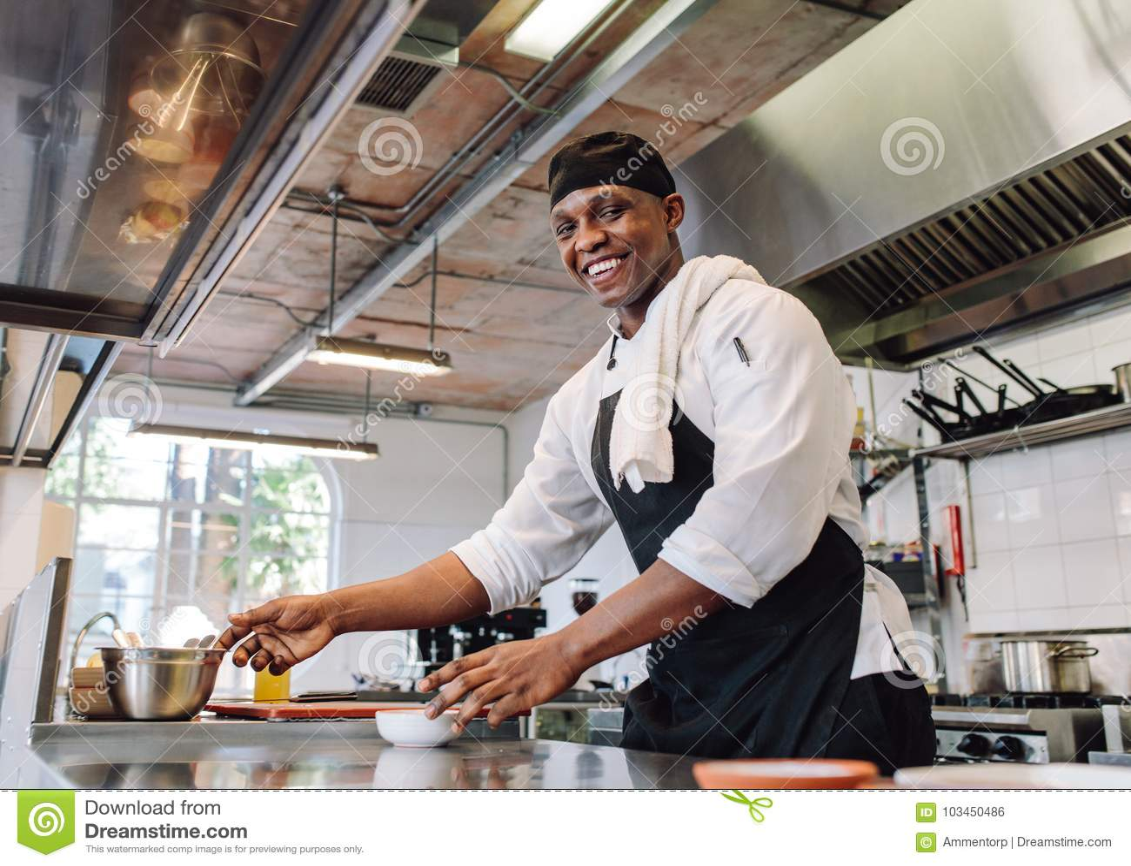 Cocinero sonriente que cocina la comida en la cocina del restaurante