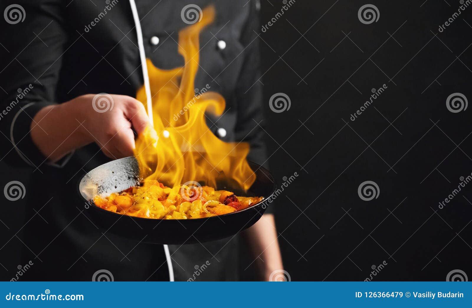 Cocinero y fuego profesionales Cocinar verduras y la comida sobre un fuego abierto en un fondo oscuro Foto del servicio de hotel