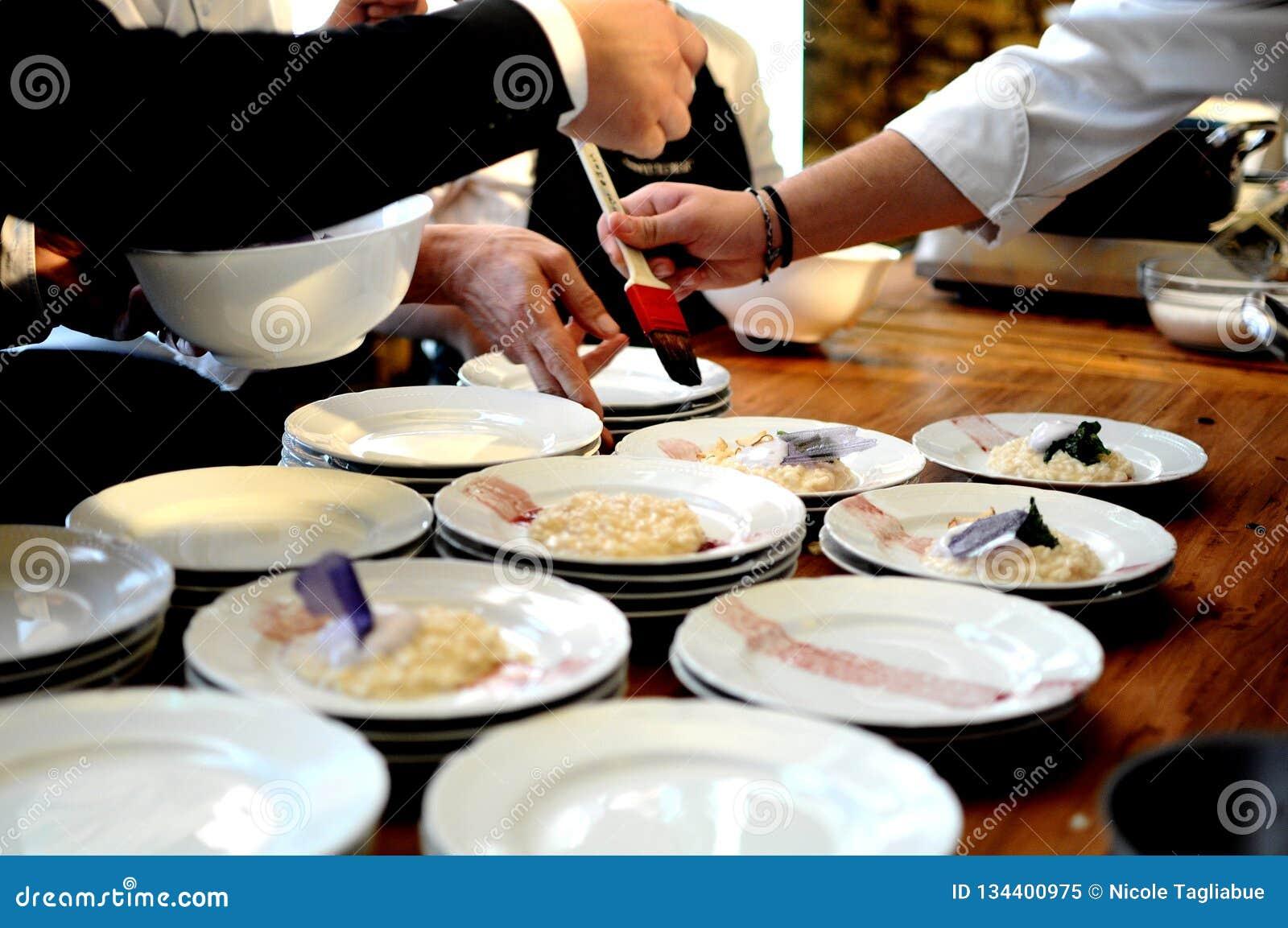 Cocineros ocupados en un restaurante que arregla y que adorna la comida deliciosa atractiva en una tabla de madera para un partid