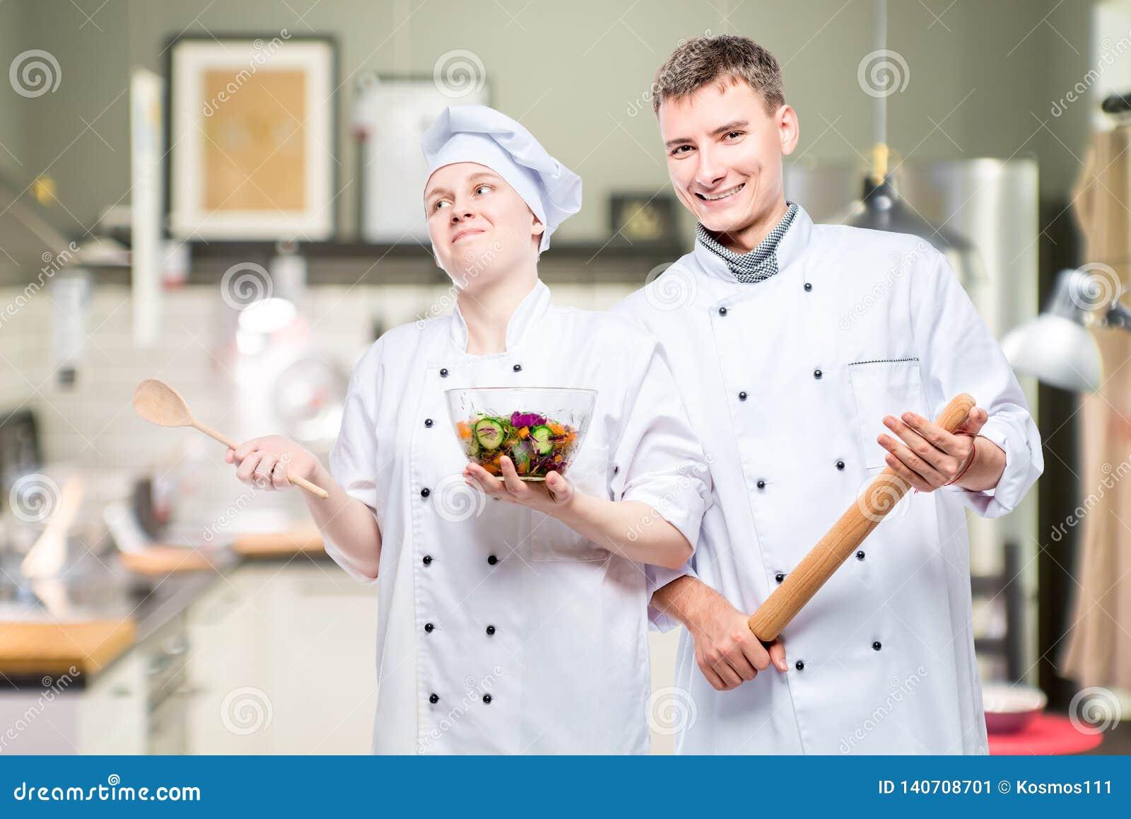 Cocineros profesionales jovenes emocionales con un plato en el fondo