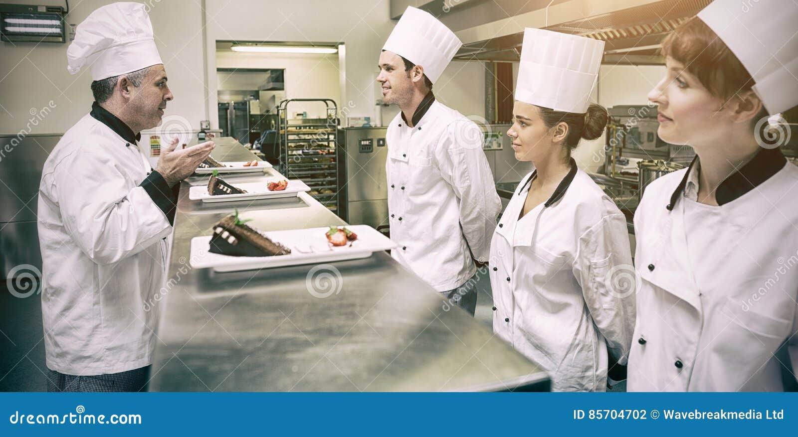 Cocineros que presentan sus placas de postre al chef en cocina